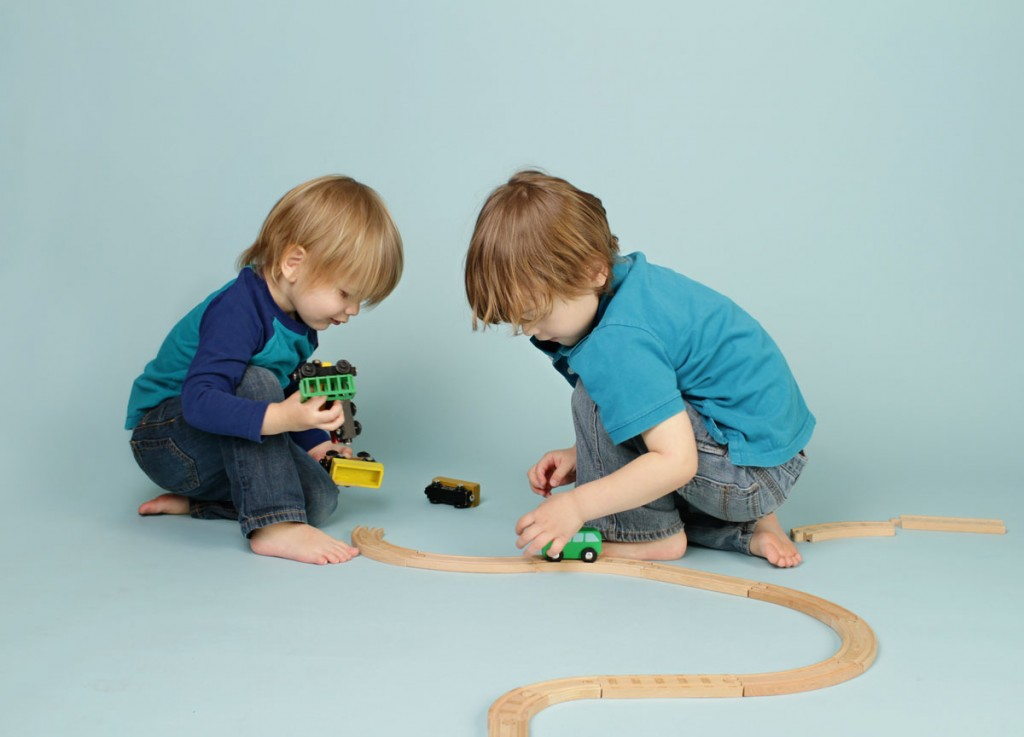 Two young boys share a toy train set.